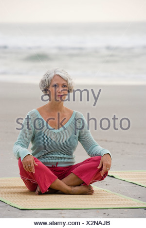 Mature woman exercising on a mat at the beach - Stock Photo