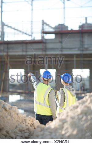 Rear view of surveyor and builder on construction site - Stock Photo