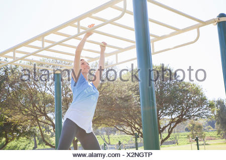 Mid adult woman training in park on monkey bars - Stock Photo