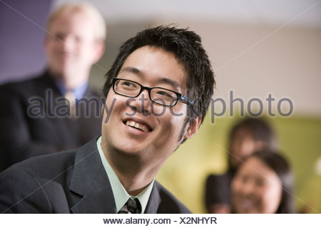 Asian businessman smiling, businesspeople in background - Stock Photo