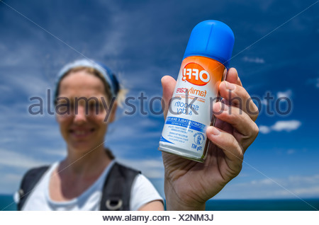 Young woman holding a can of insect repellent in her hand, New Zealand, Oceania - Stock Photo