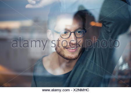 Young man looking out of window - Stock Photo