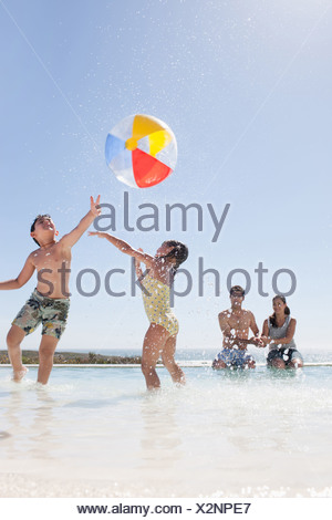 Family playing with ball in swimming pool - Stock Photo