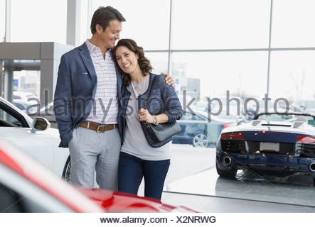 Couple hugging in car dealership showroom - Stock Photo