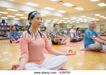 Group in lotus position in yoga class - Stock Photo
