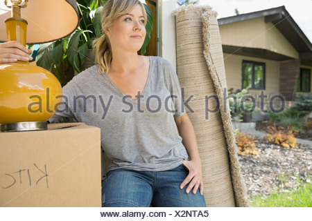 Woman unloading belongings from moving van - Stock Photo