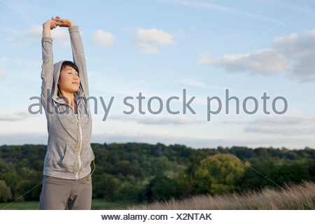 Young female runner stretching arms - Stock Photo