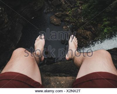 Low Section Of Man Sitting On Cliff By Waterfall In Forest - Stock Photo