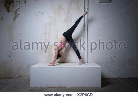 Mid adult woman practicing one legged downward facing dog position on concrete block, Munich, Bavaria, Germany - Stock Photo