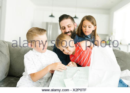 Family with three children (2-3, 6-7) celebrating fathers day - Stock Photo