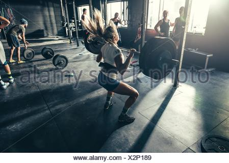 Woman training with barbell in gym - Stock Photo