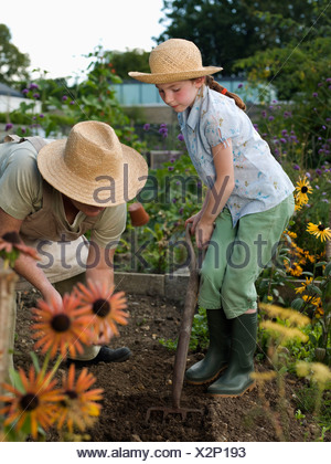 A young girl and woman work in allotment - Stock Photo