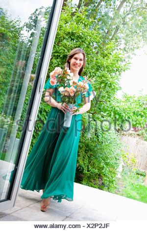 Young woman wearing green dress holding vase of flowers