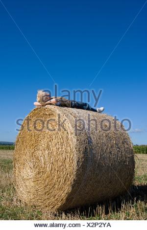 Boy (7-9) lying on hay bale in field - Stock Photo