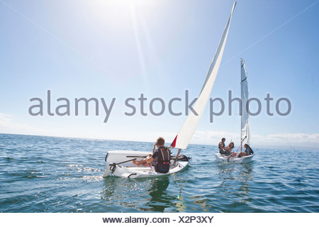 Young adult friends racing each other in sailboats - Stock Photo