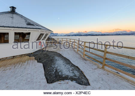 Wooden walkway and terrace on the cold sea surrounded by snowy peaks at sunset Hamn i Senja Bergsfjordens Tromsø Norway Europe - Stock Photo