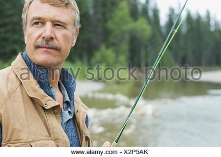 Portrait of mature man fishing - Stock Photo