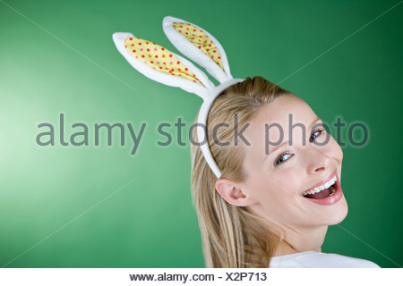 A young blonde woman wearing bunny rabbit ears, smiling - Stock Photo