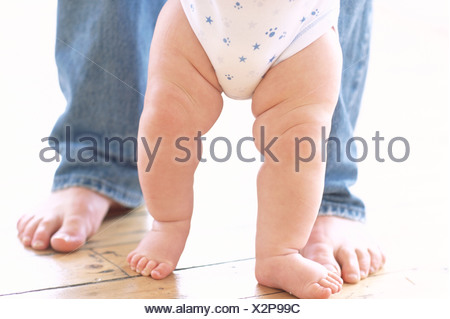 Baby's legs. Legs of a 6-month-old baby boy who is being supported by his father. - Stock Photo