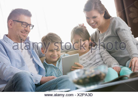 Happy family using digital tablet together in living room - Stock Photo