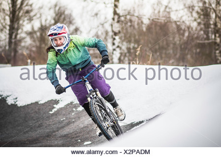 Young female mountain biker riding in snow - Stock Photo
