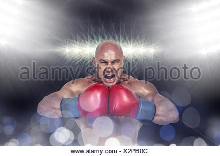 Composite image of aggressive boxer flexing muscles - Stock Photo