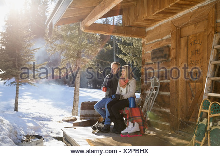 Couple sitting on cabin porch in winter - Stock Photo