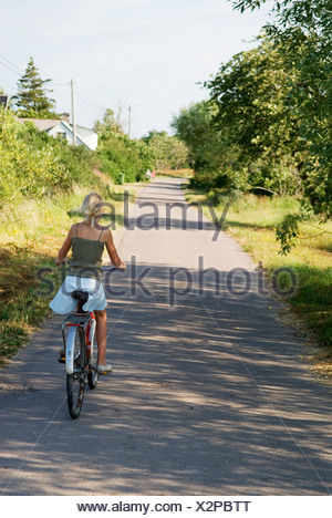 Rear view of a young girl riding bicycle on country asphalt road along trees - Stock Photo