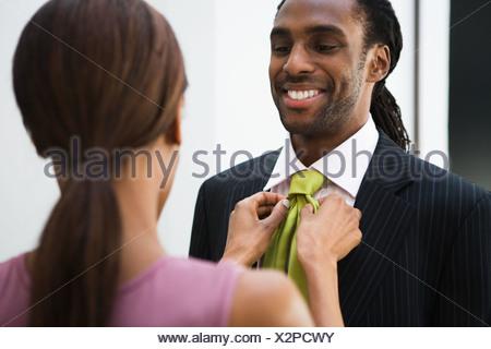 African woman adjusting husband's necktie - Stock Photo