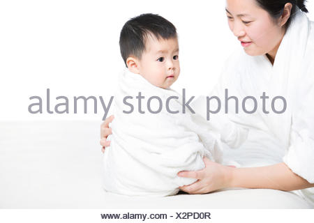 Mother wrapping baby in blanket - Stock Photo