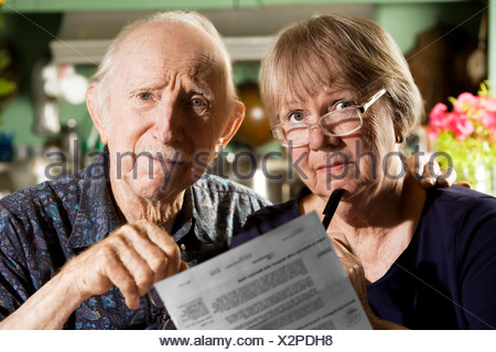 Elder Couple at Home with Bills - Stock Photo