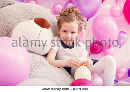 Smiling girl sits leaning on big teddy bear - Stock Photo