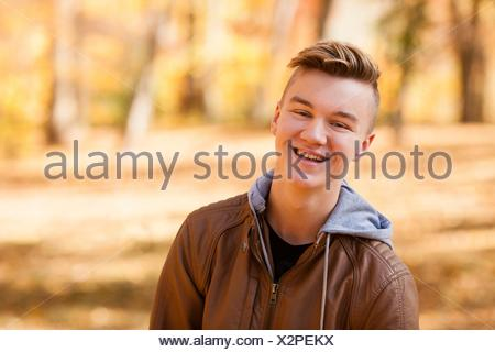 Head and shoulder portrait of teenage boy wearing leather jacket in autumn forest - Stock Photo