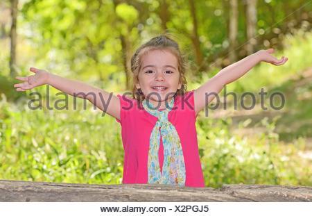 little girl enjoying and raising her hands in park. - Stock Photo