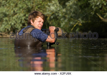 Wildlife photographer, Bertie Gregory, photographing great crested grebes while submerged in a river. - Stock Photo
