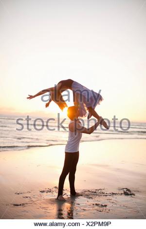 Young man lifting dancing partner on sunlit beach