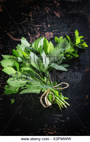 Bunch of fresh mint over black wooden table. Top view. - Stock Photo