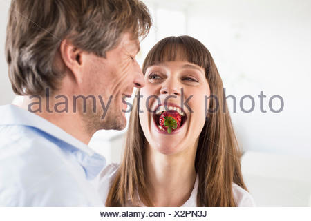 Mid adult woman carrying strawberry in mouth while man smiling, close up - Stock Photo