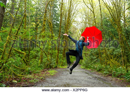 Jumping woman in forest with red umbrella - Stock Photo