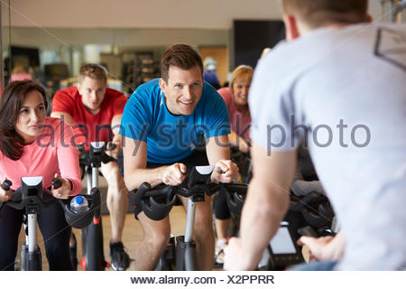 Instructor in foreground with spinning class at a gym - Stock Photo
