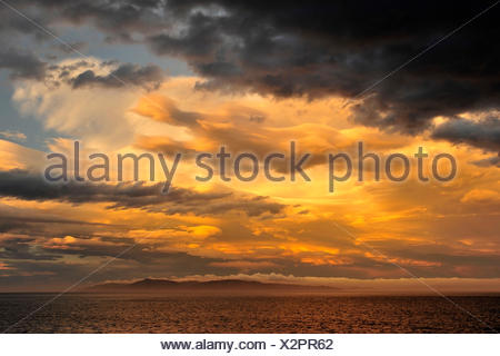 Dramatic light mood with rain clouds over the sea and an island disappearing in fog with New Zealand. - Stock Photo