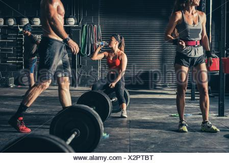 Woman sitting on barbell drinking water in gym - Stock Photo