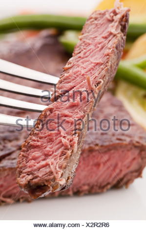 Chopped beefsteak on fork with vegetable at the background - Stock Photo