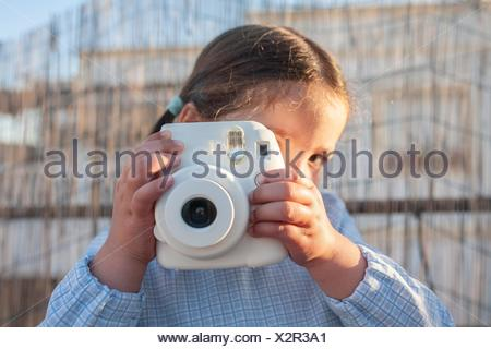 Cute little happy girl with instant picture photo camera. Outdoor. - Stock Photo