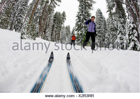 Low angle view of cross country ski tips and two young women nordic skiing on a cross country trail in the snow in Bend, Oregon. - Stock Photo