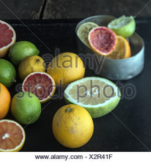Juicing a selection of fresh citrus fruit with grapefruit, oranges, limes and lemons and a metal container with squeezed skin remnants - Stock Photo