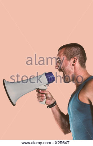 Composite image of angry male trainer yelling through megaphone - Stock Photo