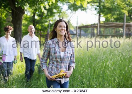 Organic farm. Summer party. Two mature people, a couple and a young woman walking through the long grass. - Stock Photo