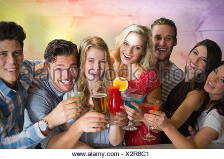 Composite image of friends drinking cocktails - Stock Photo