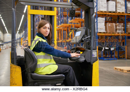 Worker operating forklift in warehouse - Stock Photo